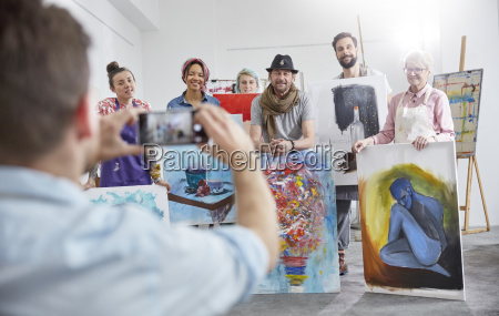 man photographing art class classmates in