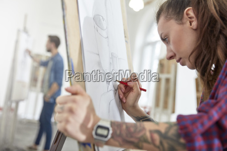 focused female artist with tattoo sketching