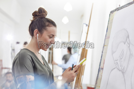 smiling female artist with headphones listening