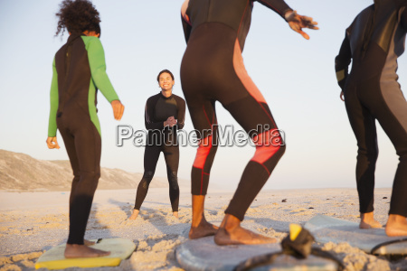 young female surfer teaching family surfing