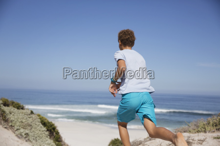 pre adolescent boy running on sunny