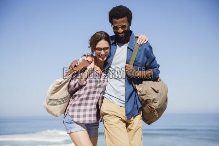 smiling affectionate mutli ethnic couple walking