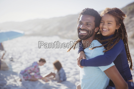 smiling affectionate father piggybacking daughter on