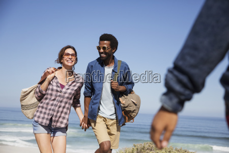 smiling multi ethnic couple holding hands
