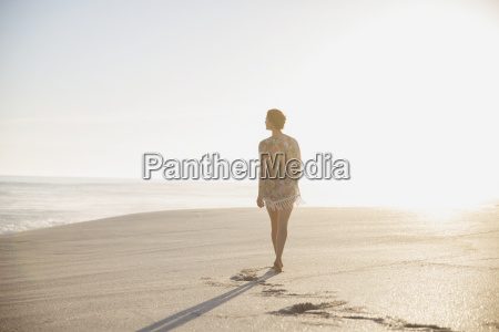 pensive serene woman walking on sunny