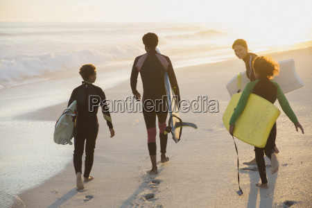 multi ethnic family carrying surfboard and