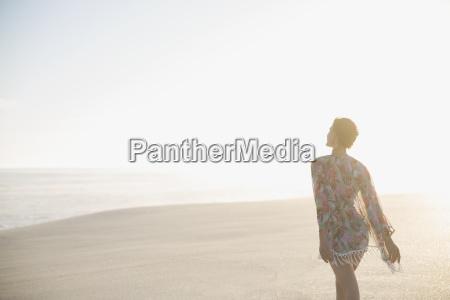 serene woman in swimsuit coverup walking