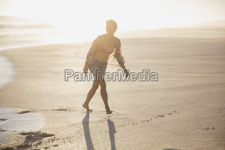 smiling woman walking on sunny sandy