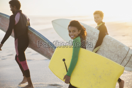 portrait smiling family carrying surfboards and