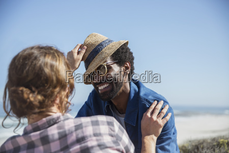 playful multi ethnic couple with hat
