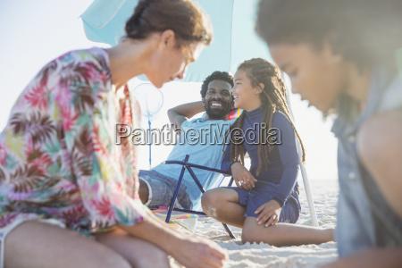 family relaxing on sunny summer beach