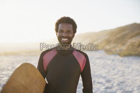 portrait smiling confident male surfer with