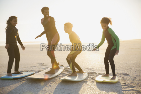 family surfers practicing on surfboards on