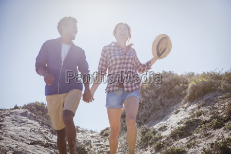 multi ethnic couple walking holding hands