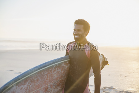 smiling male surfer walking with surfboard