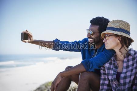 multi ethnic couple taking selfie on