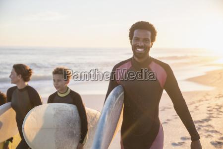 portrait smiling confident male surfer carrying