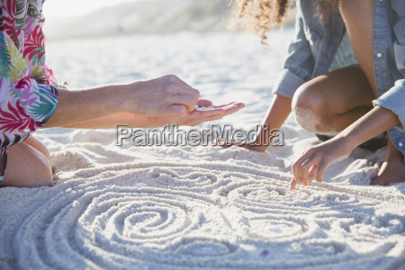 mother and daughter placing seashells in