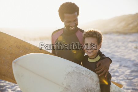 portrait smiling father and son surfers