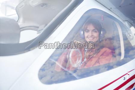 portrait smiling female airplane pilot in