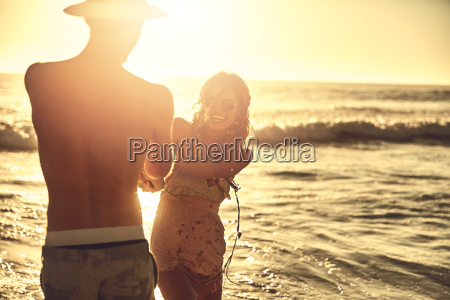 playful young couple holding hands on
