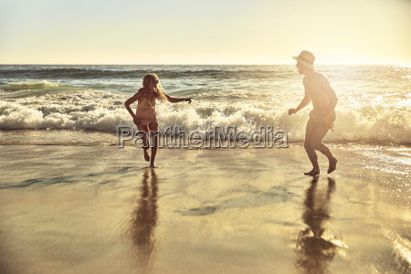 playful young couple running in wet