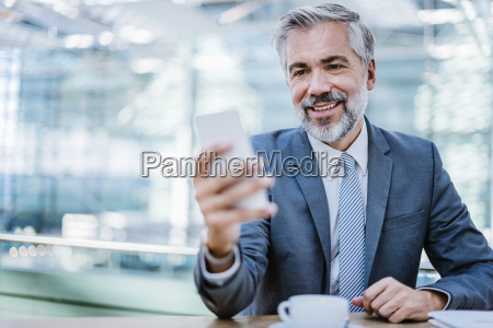 smiling businessman in a cafe looking