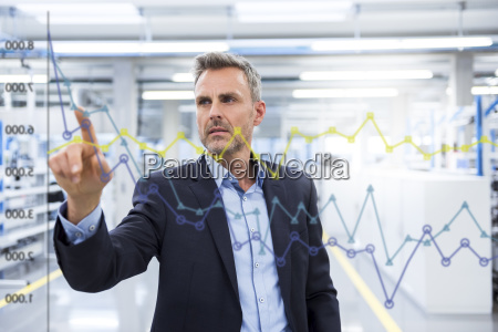 businessman looking at graph on glass
