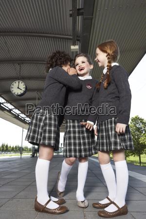 three girls at platform wearing school