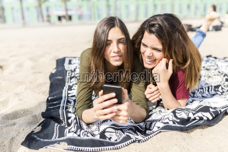 two happy female friends using cell