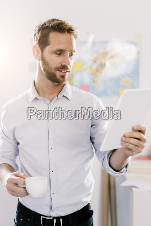bearded man in office with cup