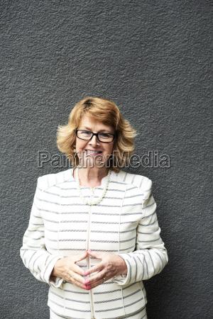 portrait of smiling senior businesswoman against