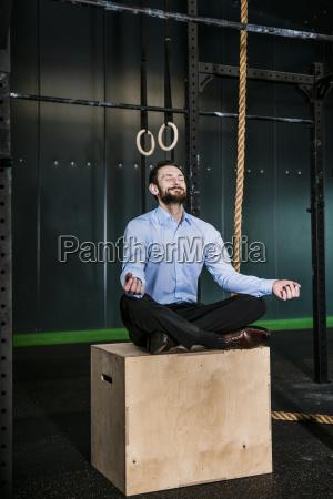 businessman in gym siting on box