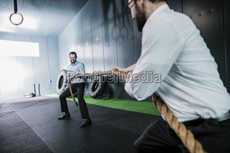 two businessmen in gym doing tug