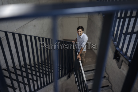 smiling young man standing in staircase