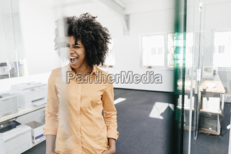 excited young woman screaming in office