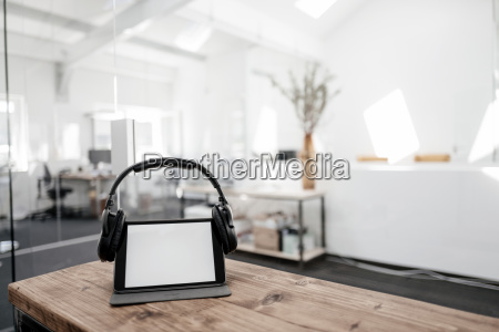 tablet with headphones on wooden table