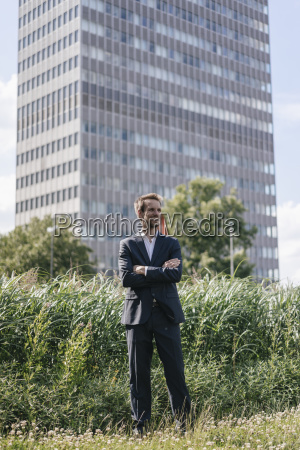 smiling businessman standing on field in
