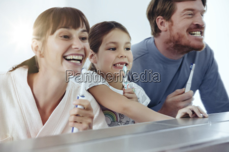 family of three brushing their teeth