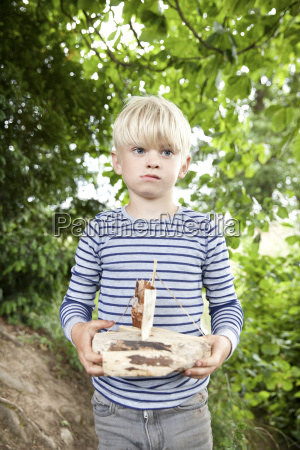 boy holding carved wooden boat in
