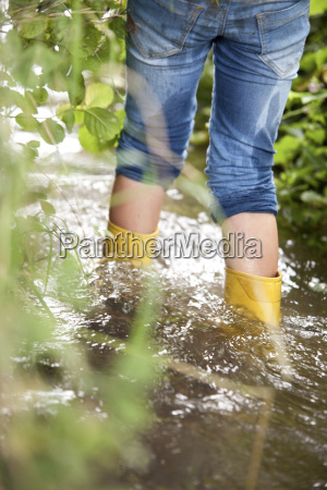 girl with rubber boots wading in