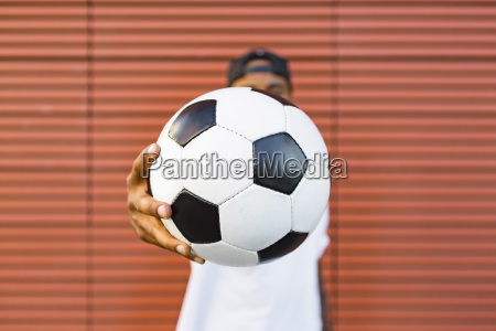 mans hand holding soccer close up