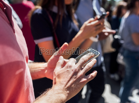 mans hand using smartphone on the