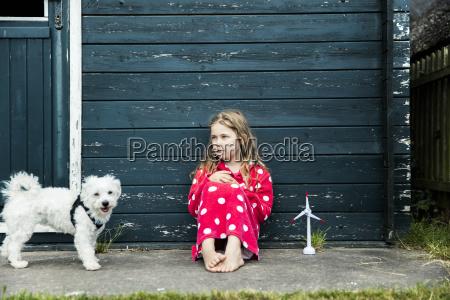 girl wearing bathrobe outdoors sitting at