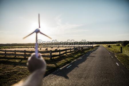 hand holding miniature wind turbine