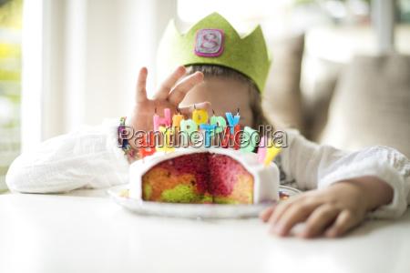 girl hiding behind birthday cake