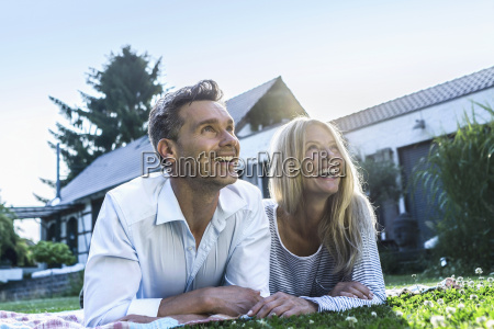 happy couple lying on grass in