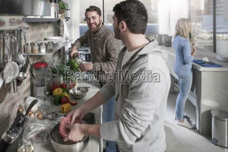 friends preparing meal in kitchen