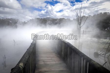 bridge on a misty lake in
