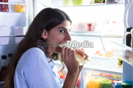 woman eating slice of cheese